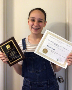 Rebeka holing two certificates and smiling