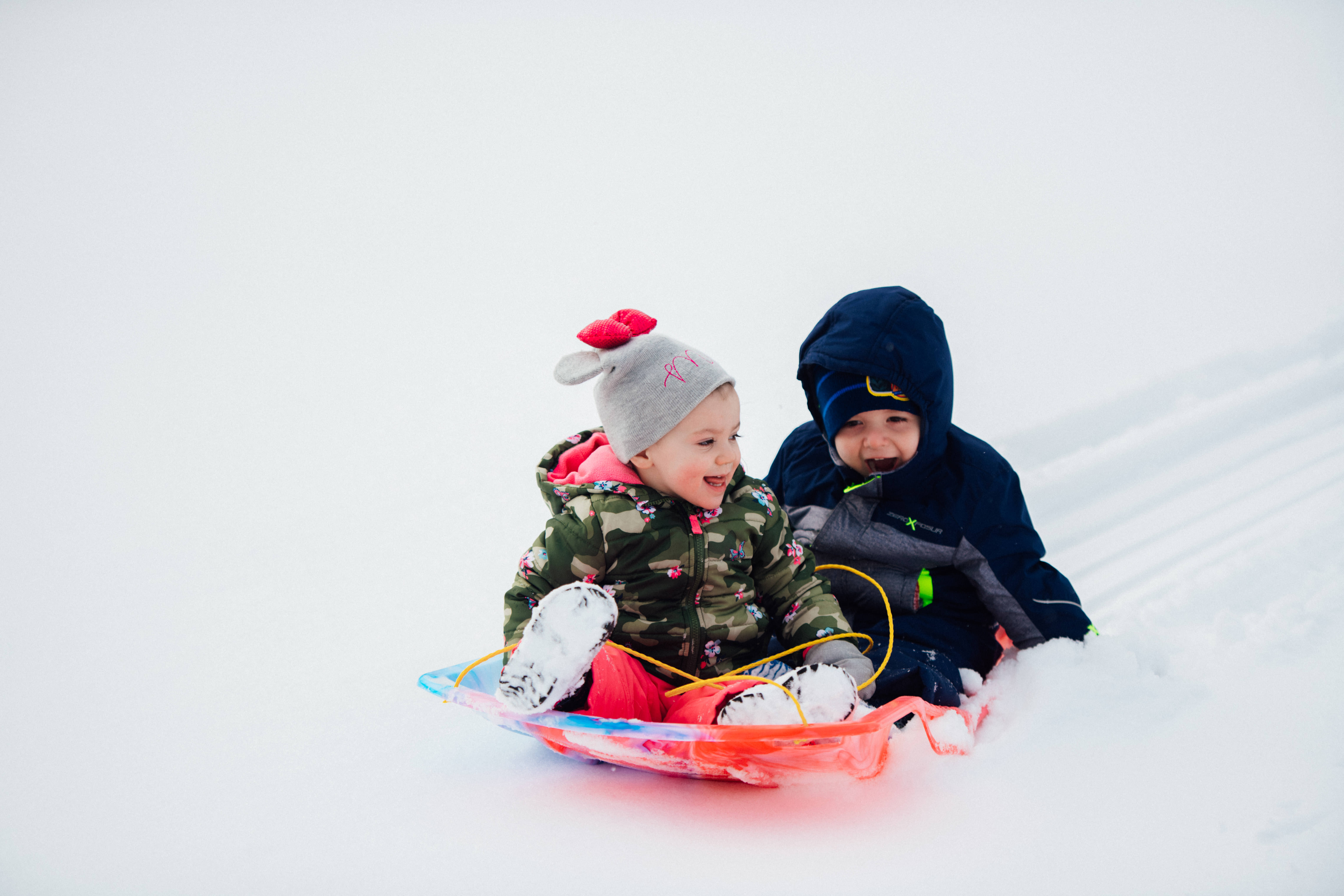 Two Little Sprouts sliding down the snow hill