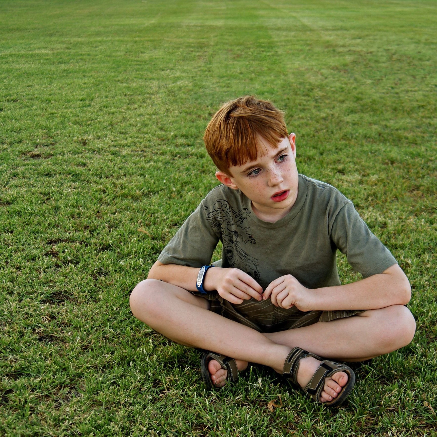 An 8-year-old boy sits on a grassy field and looks off out of frame