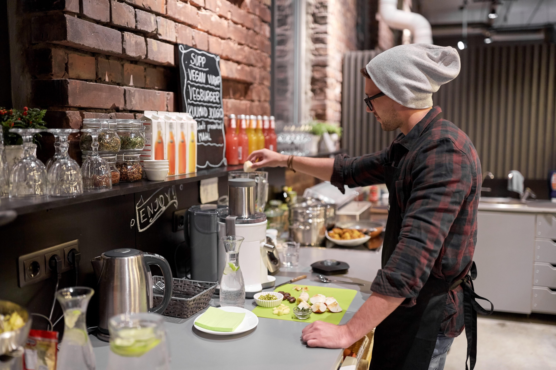 man or barman cooking smoothie at vegan cafe