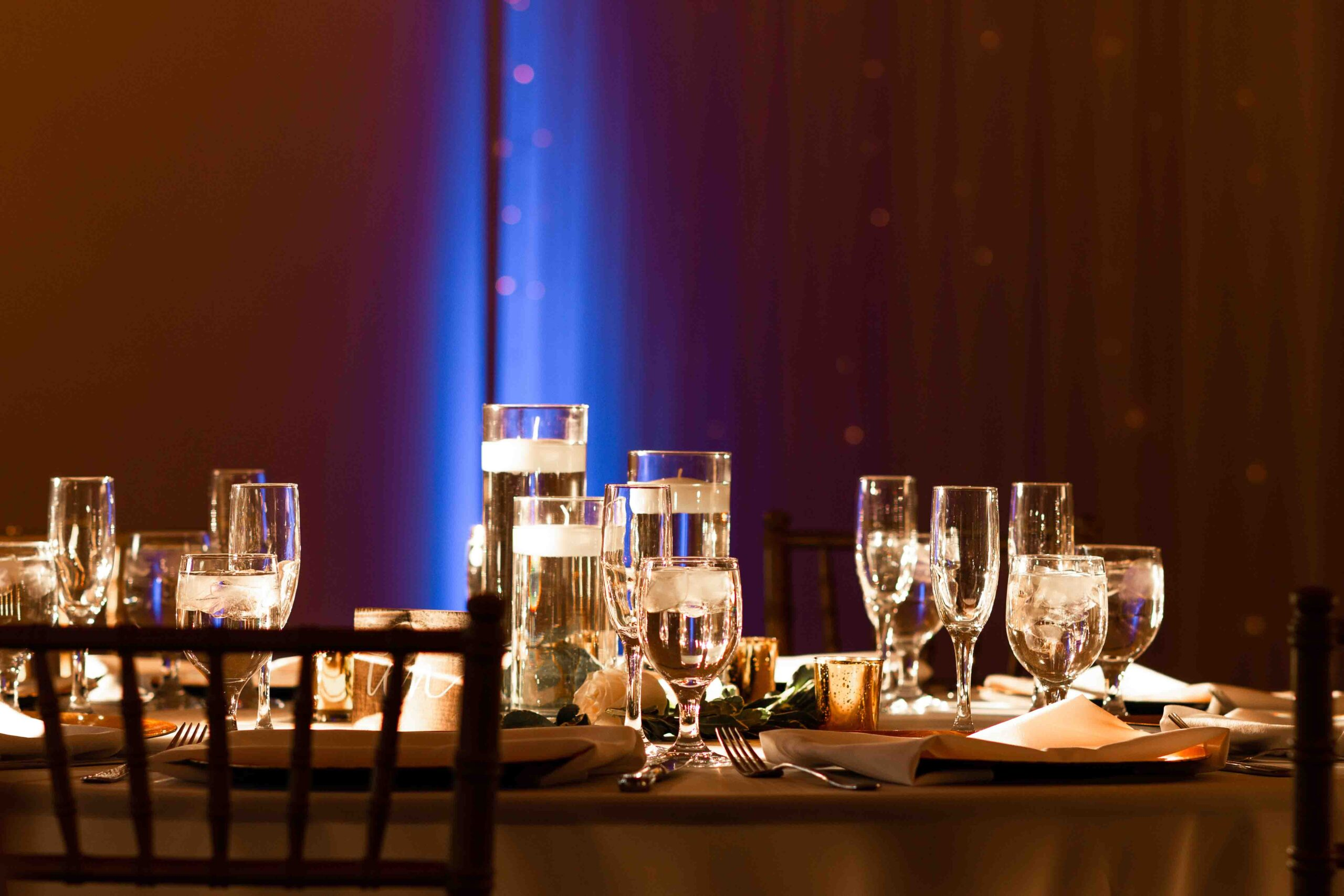 glass silverware and plates at a wedding with blue uplighting in the background