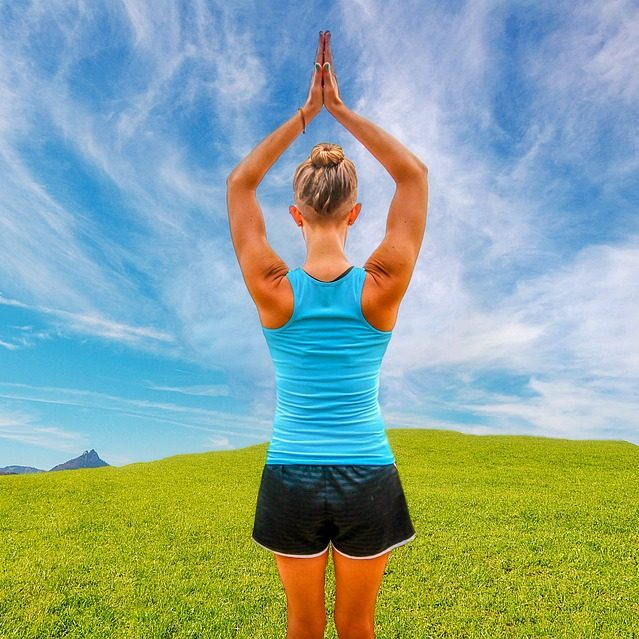 Yoga woman in a grass field