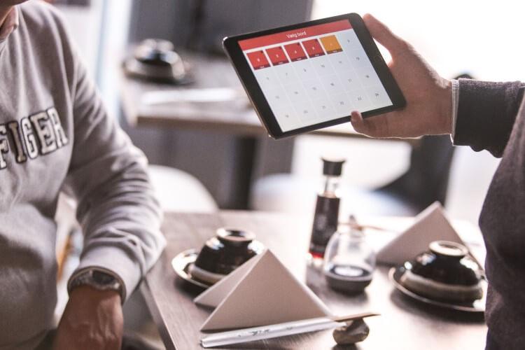 Pessoa utilizando um software PDV em um tablet.