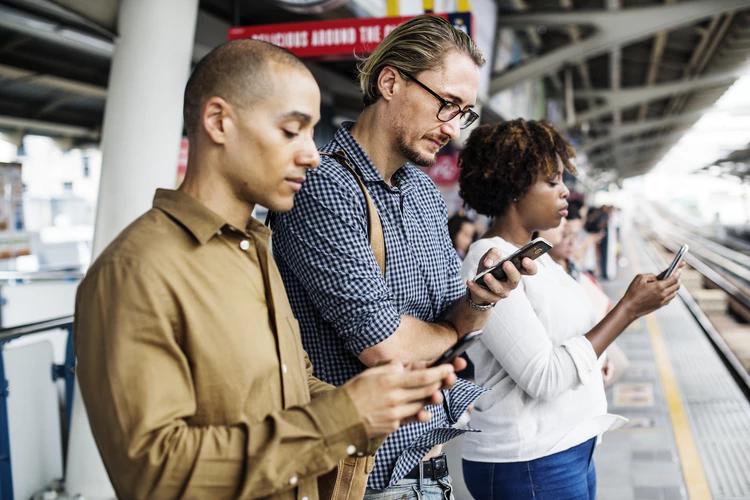 Pessoas mexendo no celular e realizando engajamento nas redes sociais.