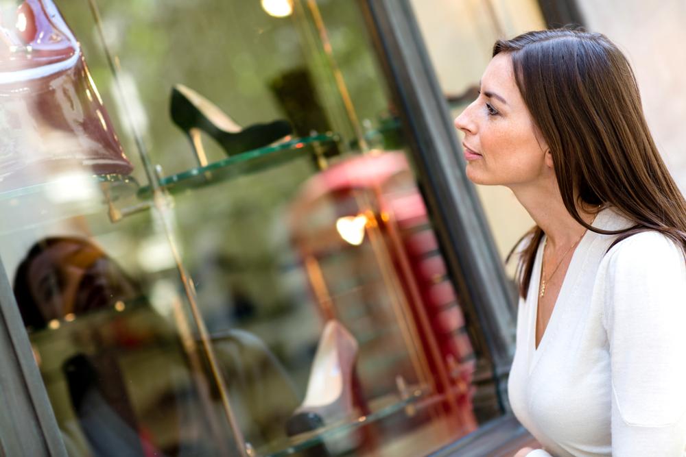 Consumidora olhando a vitrine e esperando a abordagem do cliente por parte do vendedor.