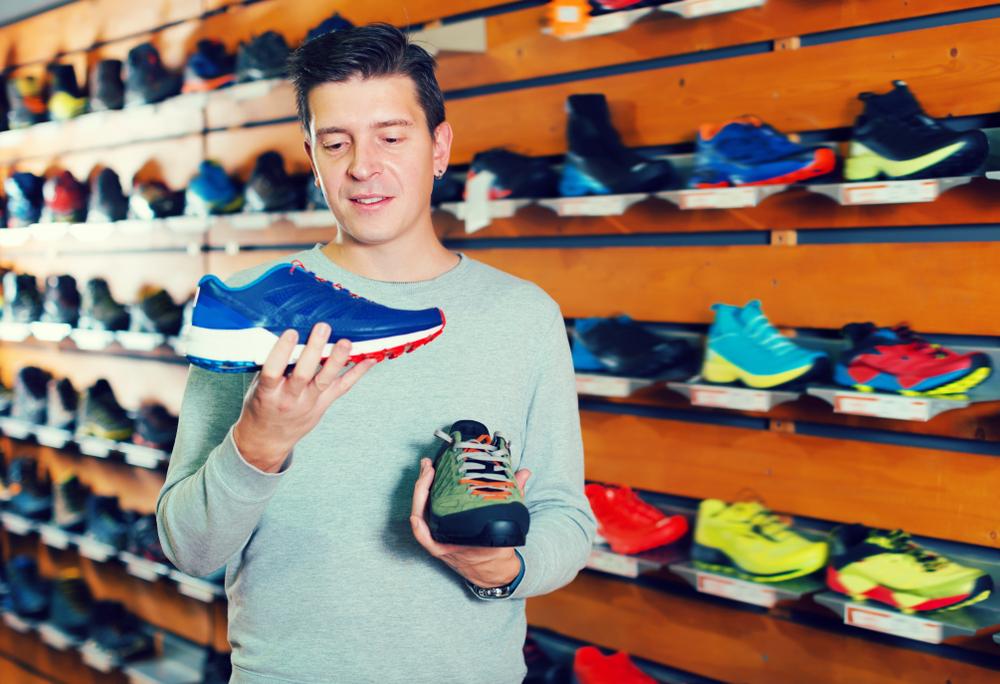 Consumidor segurando um calçado e decidindo se comprará após a abordagem ao cliente por parte do vendedor.