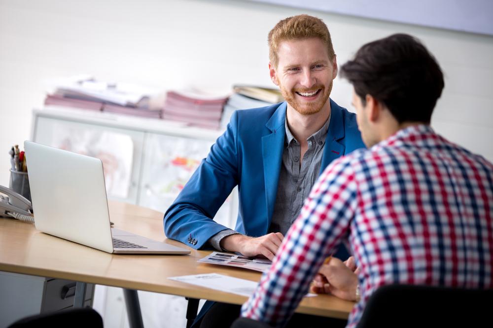 Vendedor e consumidor sorrindo durante a abordagem ao cliente.