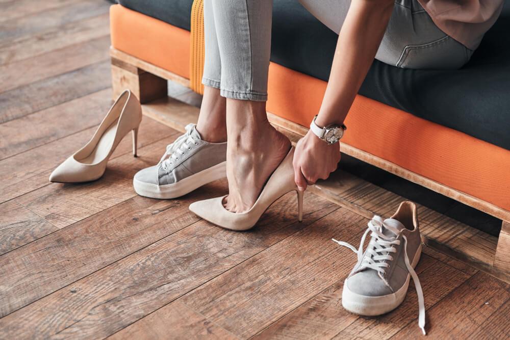 Mulher colocando um calçado de salto em loja.