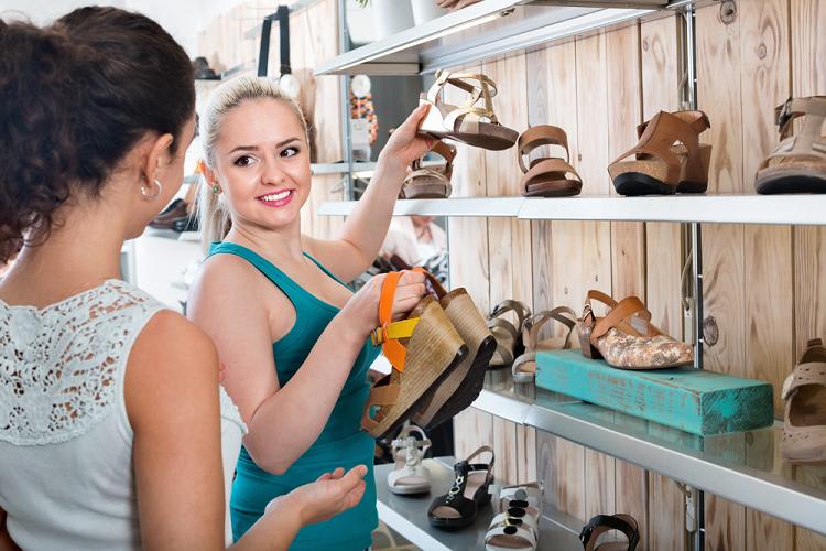 Atendente demonstrando diferentes calçados para mulher.