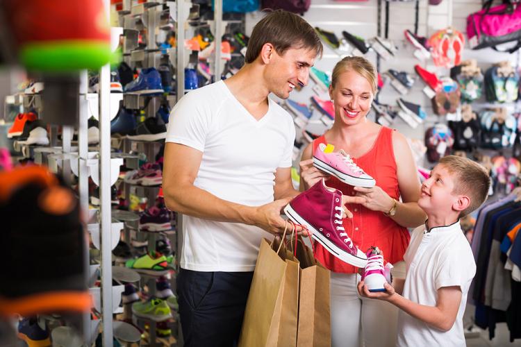 Vendedor mostrando tênis para revender calçados infantis para mãe e filho.