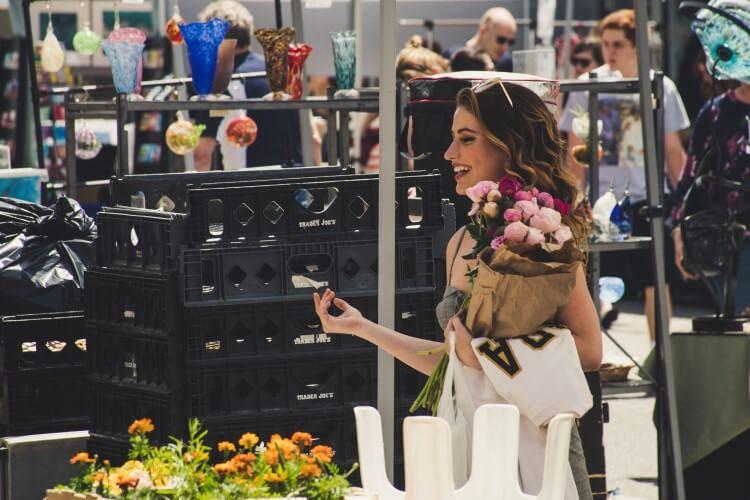 Cliente sorrindo dentro de uma loja, segurando um buquê de flores.