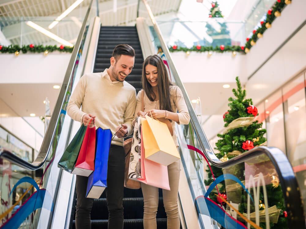 Casal hetero descendo escada rolante de shopping.