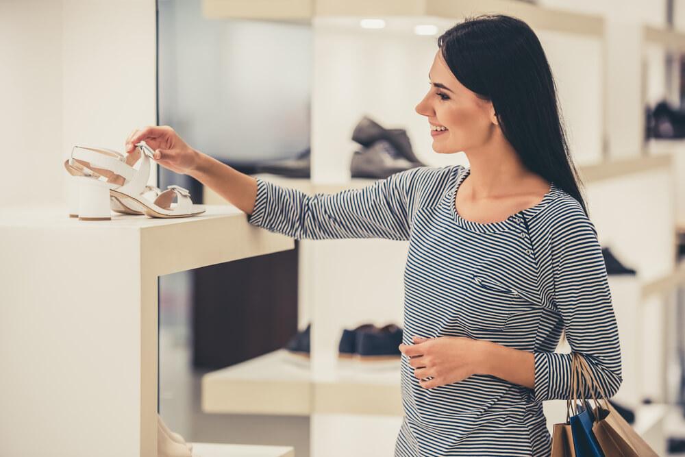 Mulher observando calçado em loja, com um sorriso.