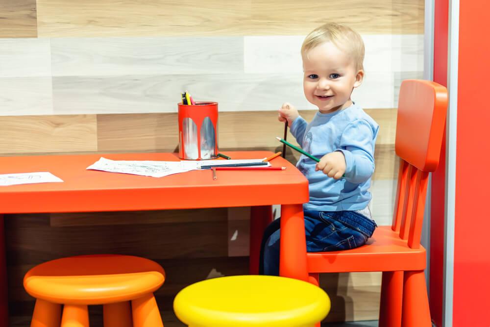 Bebê nos espaço kids desenhando: uma das ideias para o Dia das Mães no comércio