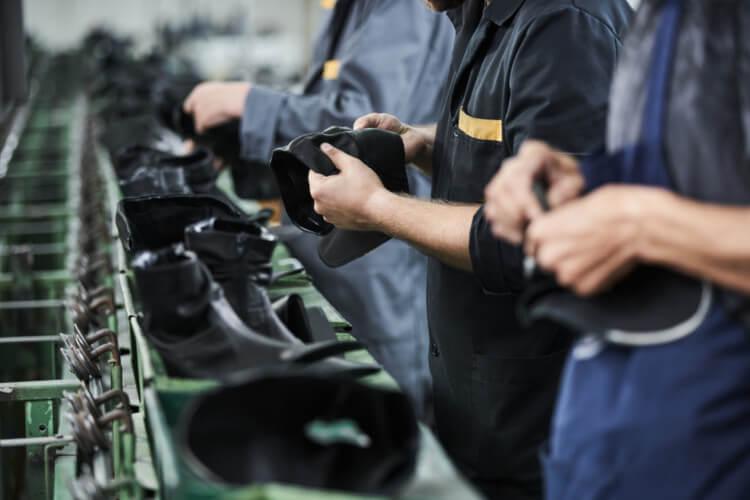 Pessoas trabalhando na linha de produção de calçados.