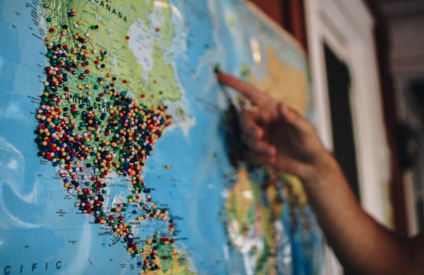 Alfinetes marcando lugares em um mapa mundi.