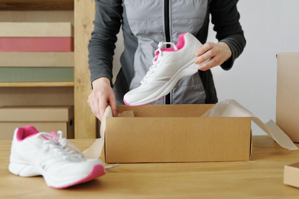 Mulher abrindo uma embalagem de calçados com tênis dentro.