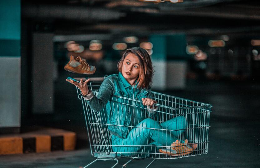 Mulher dentro de um carrinho de compras com um calçado nas mãos.