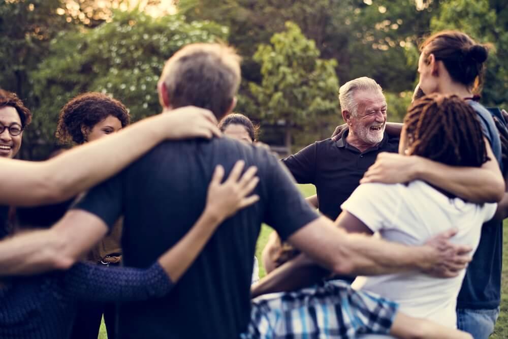 Pessoas de várias idades se abraçando.
