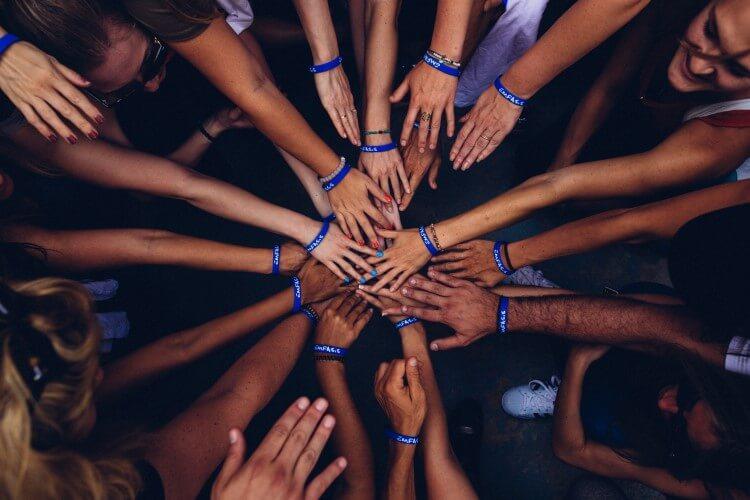 Membros de uma equipe unindo as mãos em círculo.