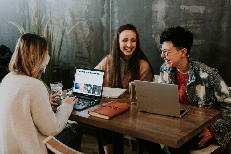 Jovens sorrindo reunidos em uma mesa de madeira com computadores e cadernos.