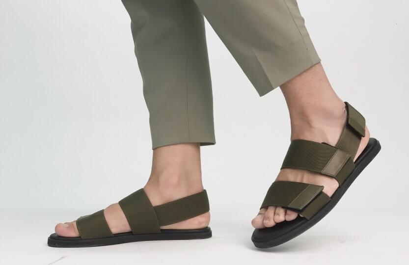 Detalhe de um modelo calçando sandálias em material sintético.