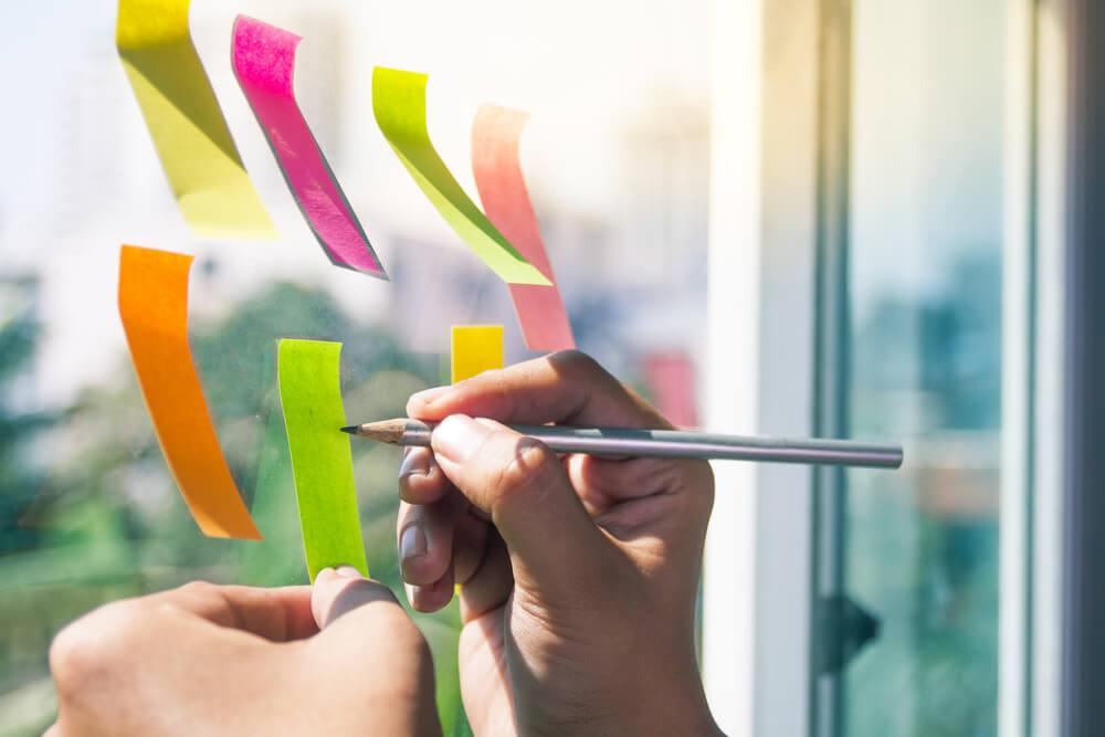 Pessoa preenchendo um post it da parede elogios que, muitas vezes, ajuda a liderar uma equipe de vendas.
