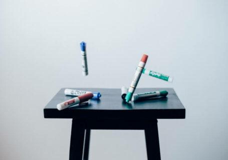 Mesa com canetões coloridos.