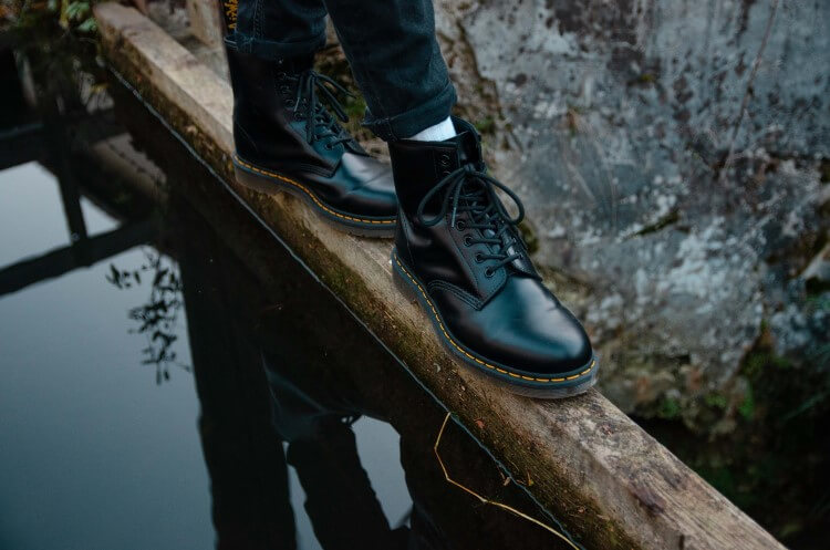 Detalhe dos pés de uma pessoa calçando botas de couro.