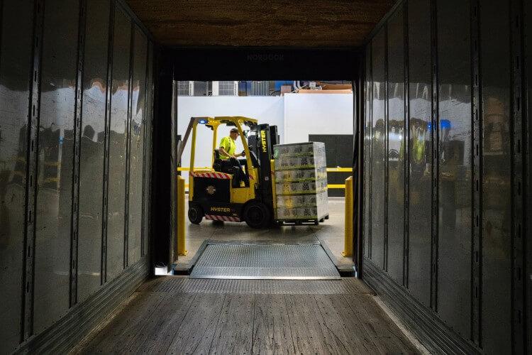 Empilhadeira carregando caixas dentro de um estoque.