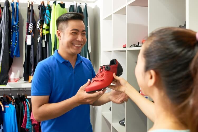 Mulher oferecendo calçado para um homem asiático na loja.