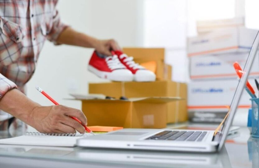 Homem coletando calçado de qualidade na caixa para envio.