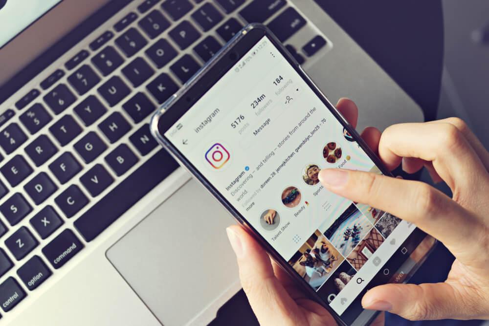 Pessoa usando o Instagram para entender como começar a vender calçados online.