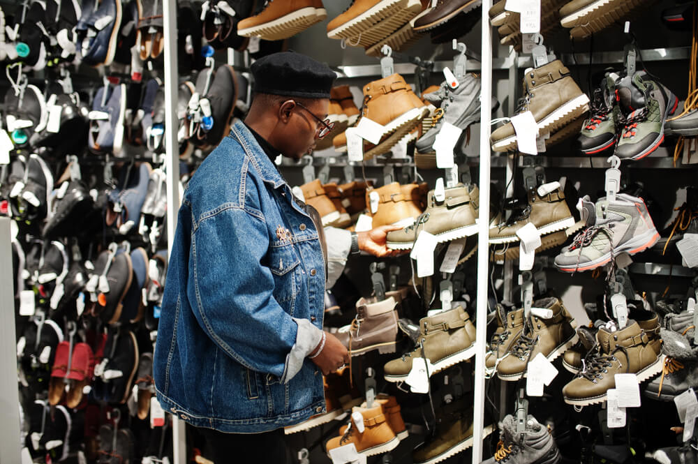 Adepto do consumo consciente de calçados escolhendo sapatos.