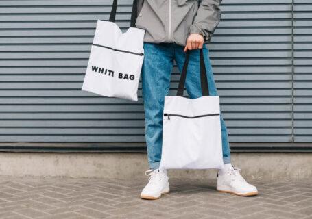 Pessoa segurando sacolas de pano e apoiando o consumo consciente de calçados e produtos.