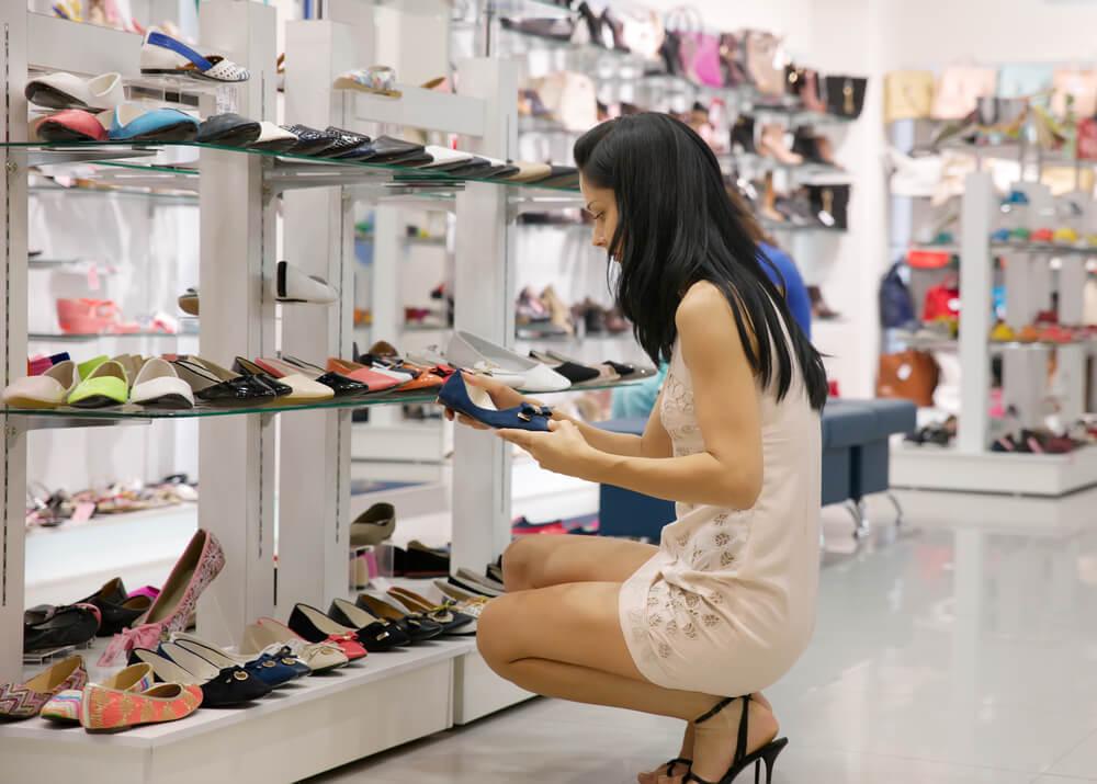 Mulher escolhendo sapato na loja pequena de calçados.