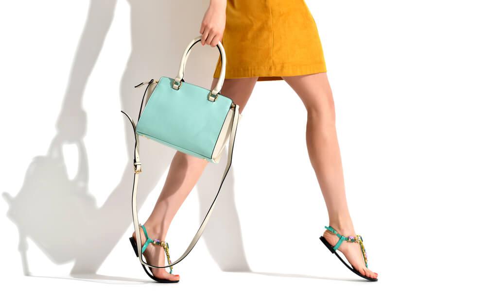 Foto de composição utilizando modelo com saia amarela, bolsa azul e sandálias azuis nos pés.