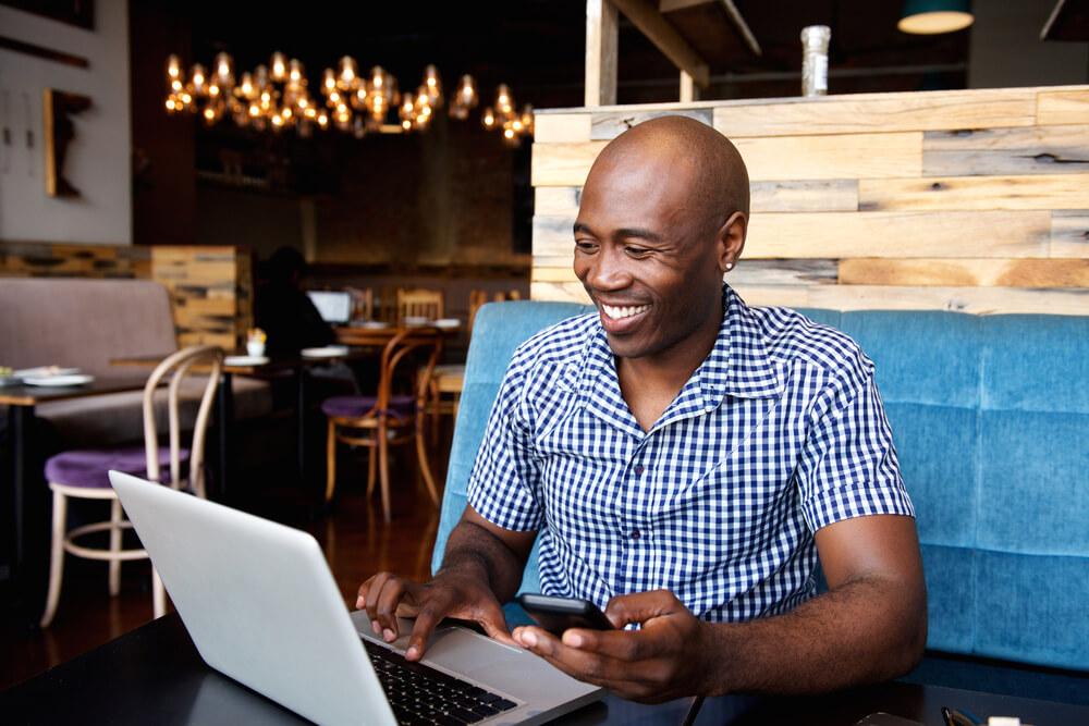 Homem negro e careca sorrindo enquanto usa o notebook e o celular em estabelecimento comercial.