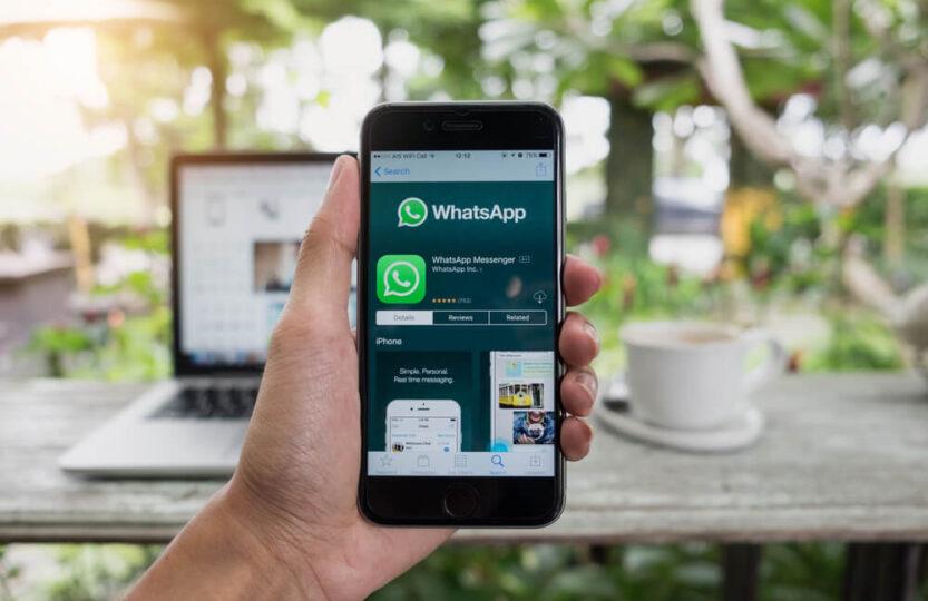 Pessoas segurando um celular com a tela para baixar o aplicativo do WhatsApp Business.