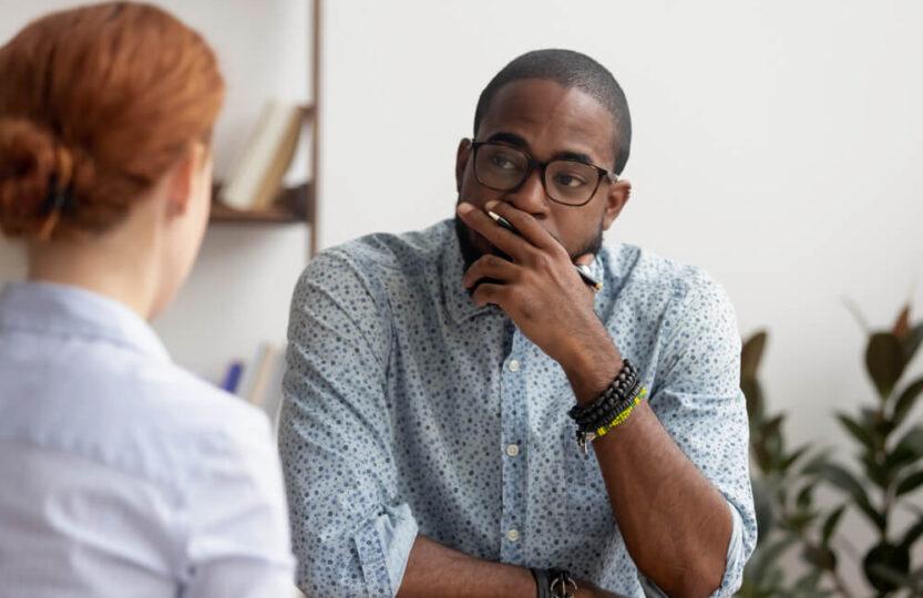 Homem negro atendendo mulher para entender como lidar com cliente insatisfeta.