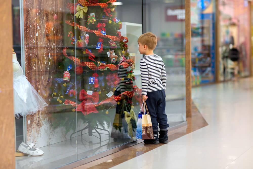 Criança olhando para vitrine da loja de calçados decorada para o Natal.