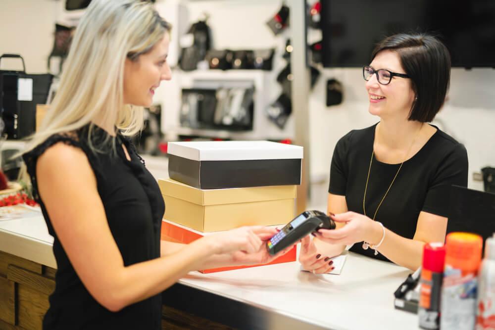Vendedora passando o cartão para cliente na loja de calçados.