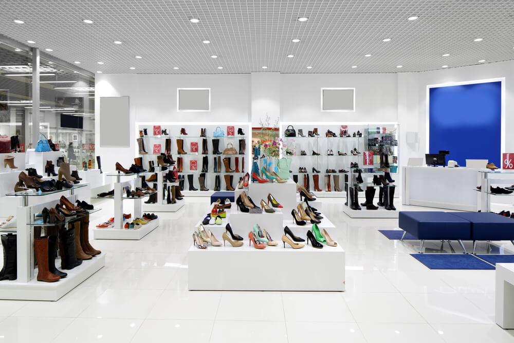 Parte de dentro de uma loja de calçados com estantes brancas e luz posicionada acima.