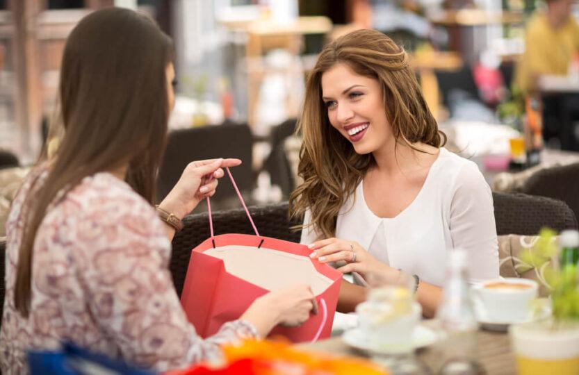 Jovem adulta finalizando sua compra de Dia da Mulher na loja de calçados.