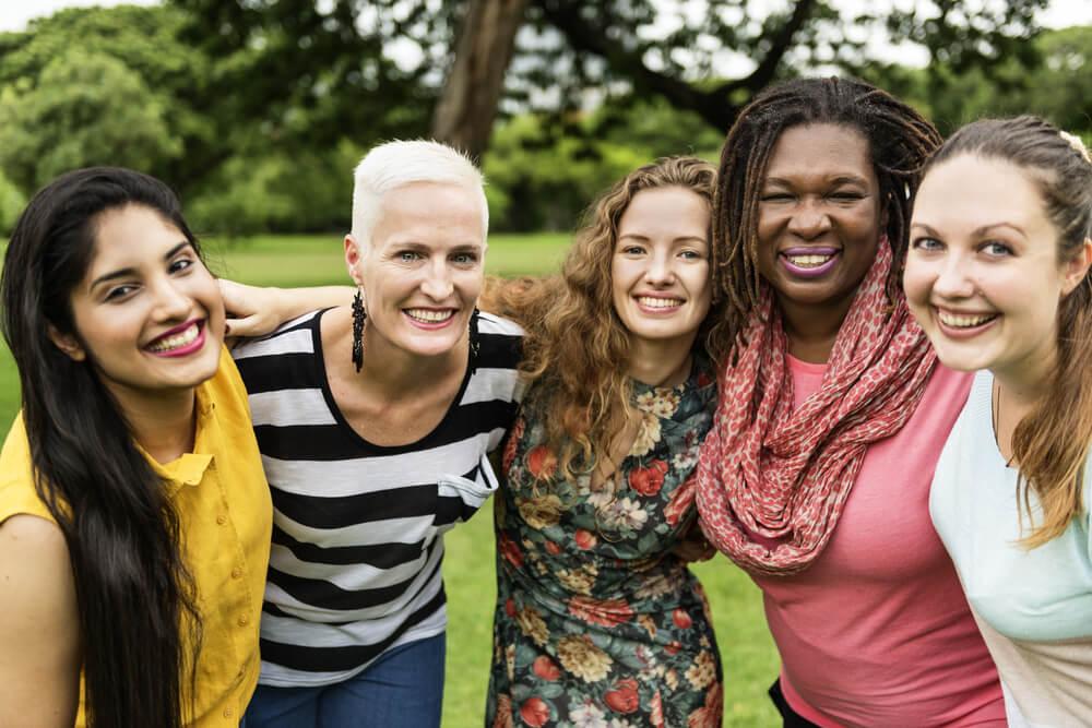 Mulheres negras, brancas, idosas, loiras e morenas reunidas em abraço.