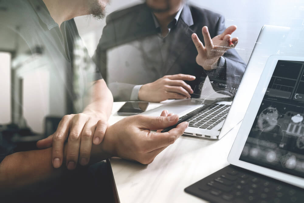 Pessoas conversando ao analisar os dados do cliente no software de gestão.