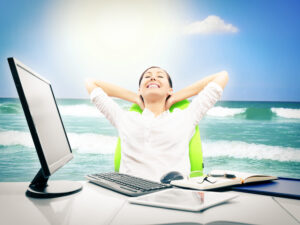 A woman sitting at her desk dreaming about vacation with an ocean background.