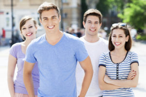 a group in teen treatment are outside smiling together