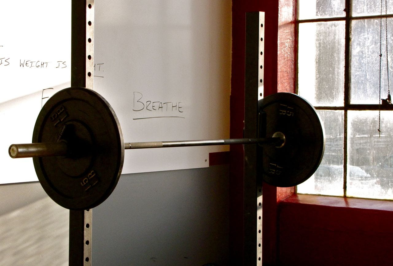 barbell and whiteboard with word breathe