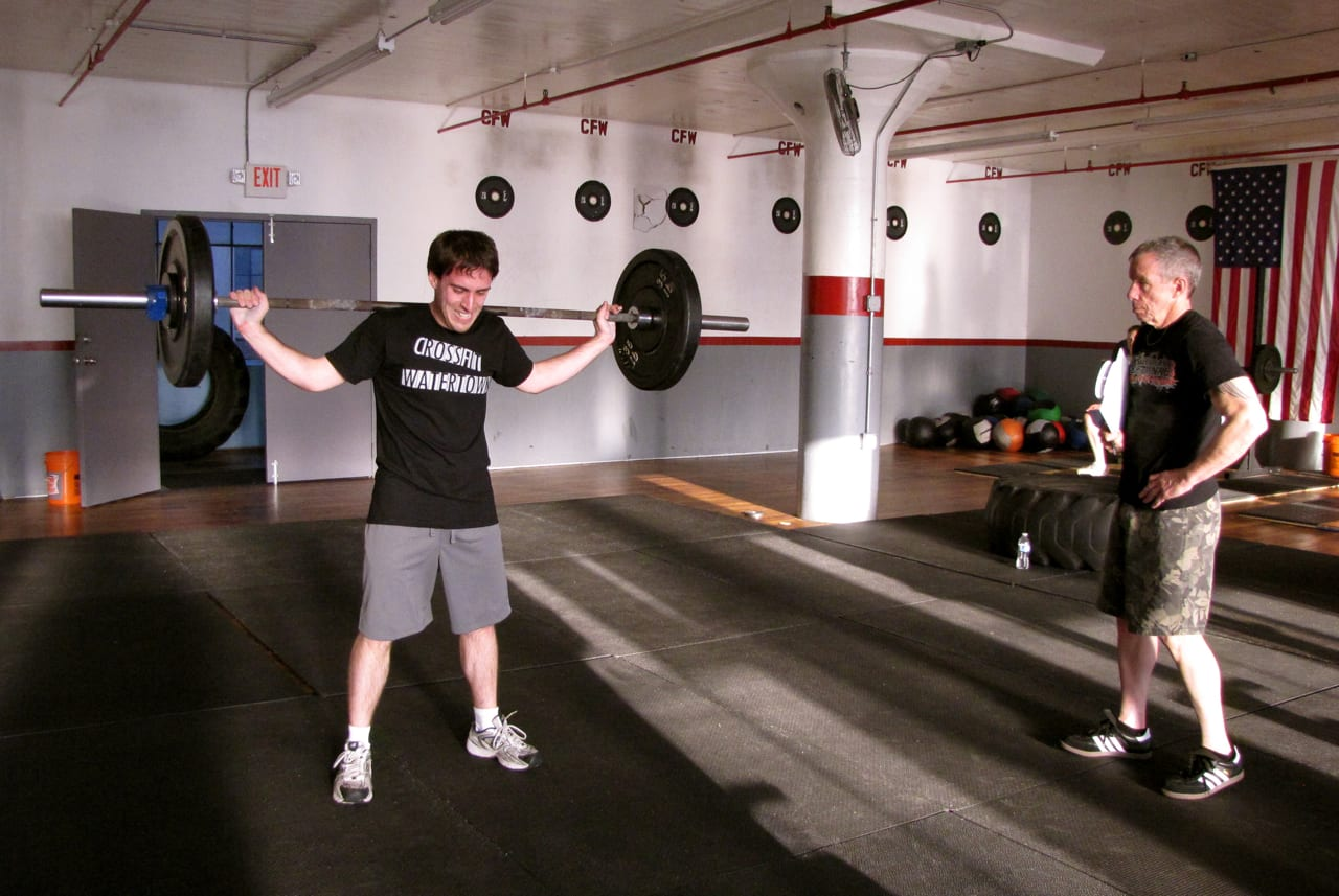 one man with a barbell while another man watches